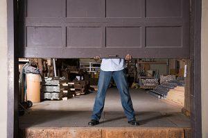 man physically lifting up garage door