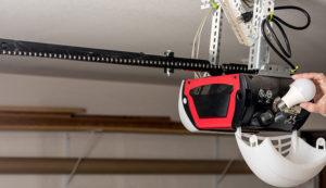 Specialist replacing a lightbulb in mounted garage door opener