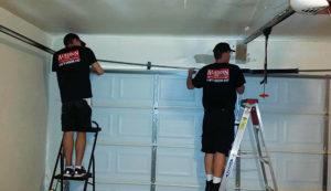 Specialists replacing a garage door spring